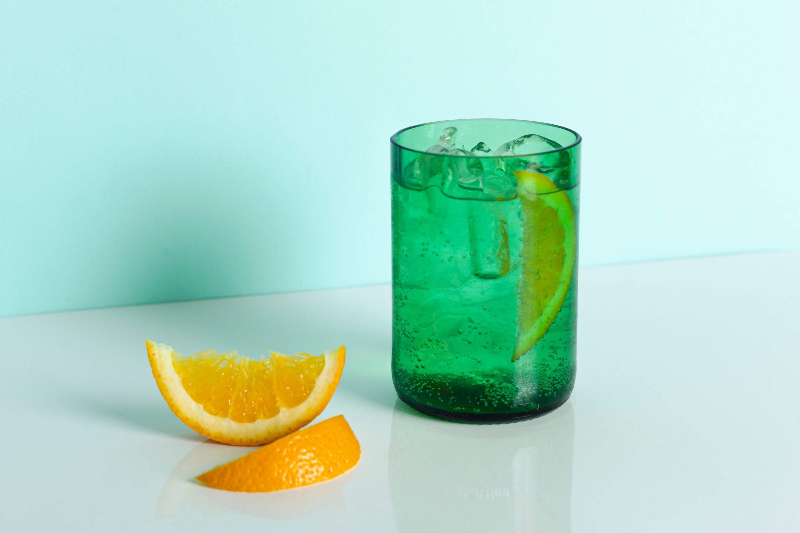Rebottled groen glas met sinaasappel schijfjes